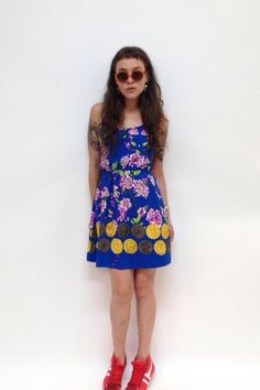 Tiki Flowers Sun Dress by Tyche. Flirty and sweet, this summer dress features vintage styling details like an adjustable tie-back top, side pockets, and retro purple floral print on a rich cobalt background.  With a bra-friendly top, cut-out back, and bold print, this is a perfect summer party dress. Virtually wrinkle proof. Pull your hair back, toss on a pair of sandals, and you're ready.  Made in Los Angeles. $42.