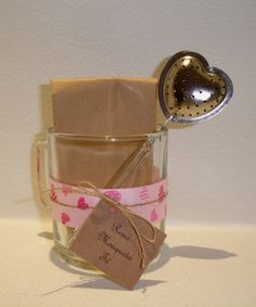 Taza de vidrio con infusor y sobre kraft con té en hebras