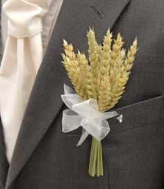 A stunning artificial dried natural wheat wedding day grooms buttonhole. Finished here with an ivory organza ribbon bow but this can be changed to suit your colour scheme.  Measurements Width:- 3.5 inches Length:- 6 inches