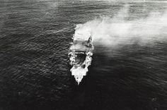 The burning Japanese aircraft carrier Hiryu photographed by a Yokosuka B4Y aircraft from the carrier Hosho shortly after sunrise on 5 June 1942. Hiryu sank a few hours later. Note the collapsed flight deck over the forward hangar.