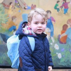 Prince George dressed in a navy quilted jacket and light blue rucksack grinned as he made ...