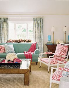 This room by Jonathan Rosen is fun, easygoing, and uncluttered. It features the same fabric in two different colors for its come-on-get-happy energy, and enjoys lots of natural light. Under glass on the coffee table is a collage of beloved photos — a space-saving method of display.