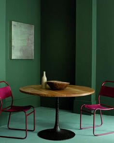 green walls, pink chairs, center table, green floor