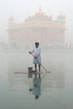 A Sikh man cleans the water tank during morning fog at the Golden Temple in Amritsar.