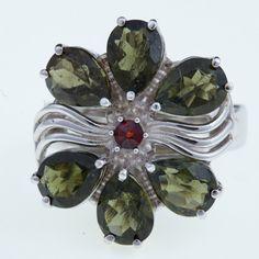 Stříbrný prsten s broušenými jihočeskými vltavíny a granátem. Ruční výroba ve tvaru květu. Materiál: Stříbro 925/1000, rhodiovaný povrch zabraňující oxidaci a černání Hmotnost: 9,16 g, Velikost vltavínu: 8×6 mm. Velikost prstenu: 57, 58