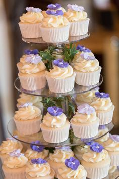 Wedding cupcake tower - vanilla cupcakes with white frosting + purple sugar flowers {Anne Lee Photography}