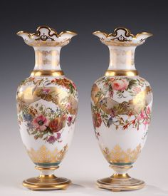 A nice pair baluster vases in white enamelled opaline decorated with polychromatic flowers heightened with gilded arabesques on the edge of the neck and on the base of each vase...