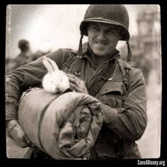 This is a photo of Cpl. Michael Deliman of the 82nd Airborne Division, seen here with his sleeping roll and Albino rabbit mascot, on the day of his return back to France; England - 11 July 1944.