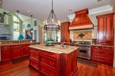 This gallery features beautiful cherry wood kitchens in contemporary, modern, rustic and traditional design styles. Kitchens with cherry wood cabinets offer a warm and luxurious look and match well with a variety of different countertop materials and finishes. This kitchen is directly open to...