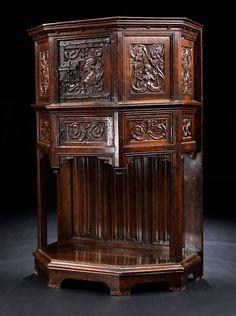 Fünfseitiger Unterbau mit zwei Stützen, die das sechseckige Oberteil tragen. Die Vorderfront mit kleiner Tür und Schlossbeschlag im gotischen Stil, seitlich ...