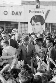 Robert F. Kennedy Reaching to Shake Hands in Crowd Original caption: Kennedy's image follows him here. A large portrait of Robert Kennedy looms behind, as the Senator shakes hands from platform after speech at shopping center. Kennedy took time out from Indiana campaign for short visit here. 25 April 1968