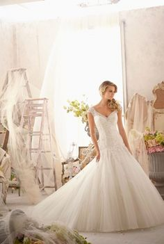 Mori Lee - Barcelona. Gorgeous gown with v-neckline and cap sleeves. Alencon lace through the bodice complements the dropped waist with appliqu�s on tulle skirt. The back of the gown features a v-back neckline and covered buttons running down and chapel length train.