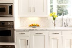 Contemporary cabinets with marble backsplash.  Hardware is nice. Beautiful Kitchen Backsplashes, Take One