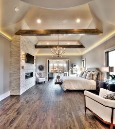 Master Bedroom- Attached to leisure room, hardwood floors, floor to ceiling fireplace, pendant chandelier, large windows with a lot of natural light