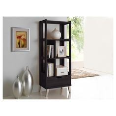 Simple and architectural, the Kalien Dark Brown Wood Leaning Bookcase is reminiscent of modern and contemporary design. The Kalien's clean and functional design features powder coated vinyl legs supporting the framework of the bookshelf. A generous sized storage drawer, two smaller open shelves, two larger open shelves and one large horizontal spanned shelf are built in providing storage solution for a better living. Crisp, clean lines and finger grooves drawer give the shelf an e...