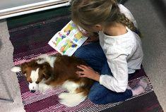 Tyttö lukee kirjaa Edske-koiran kanssa.