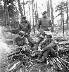 Infantrymen of the Queen's Own Cameron Highlanders of Canada sitting around a bonfire in the Hochwald, Germany, 5 March 1945. Photographer: Ken Bell.  Library and Archives Canada MIKAN 3529272
