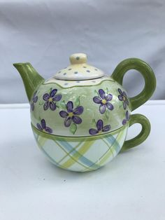 A very cut stackable tea pot and cup also known as Tea for One. A great way to carry your tea to your favorite chair. This one has purple flowers on the tea pot and green/blue/white plaid on the cup, and it is topped with a blue polka dot lid. Makes a great gift. The bottom of the Blue Green, Blue And White, Tea For One, Chocolate Pots, Blue Polka Dots, White Plaid, Purple Flowers, Tea Pots, Coffee