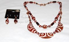 Batik Oculi - According to legend, the unique horn-shaped Batik Carnelian Tibetan dZi Beads will help with different factors of life dependent on the design of the bead. The single 2-Eye dZi Bead (left bead in picture) is known as a Love Stone. It is said to assist with family and relationship harmony. The two 3-Eye dZi Beads (central and right beads) relate to wealth and health. These are complemented by smaller Carnelian dZi Beads commonly used for Feng Shui. All of the dZi Beads are…