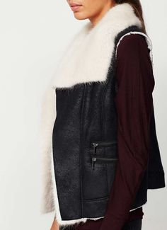 Inspired by aviator styling, add a touch of luxury in this black suedette gilet with a cream faux fur trim and zip detailing. Model is 5'10in and wears a UK size 10. The length from side neck point to hem measures 60cm/23.5in. Please note this garment is dry clean only.