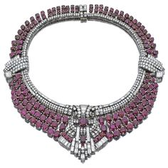 Ruby and Diamond Necklace, late 1930's | Sotheby's | The necklace set with circular-, single-cut and baguette diamonds, suspending articulated oval ruby fringes, to the stylised scroll motifs, length approximately 385mm.