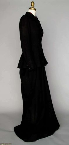 "LADY'S SIDE SADDLE HABIT, c. 1890 Black wool, fitted long jacker, red wool pieced beneath jacket collar, label on skirt ""Dark & gordon New York"". Sideway"