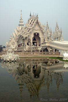 The What? - The White Wat! (by HellonEarth2006)  The White Wat otherwise known as The White Temple or The White Palace is located just outside of Chiang Rai. It is officially known as Wat Rong Khun and is the brainchild of Thai artist Chalermchai Kositpipat . The temple will conprise 9 buildings when it is finished. It was started in 1997 and has been built entirely from public donations and attracts both Thai and foreign visitors. Constructed in white and glass mosaic, it is a spectacular…
