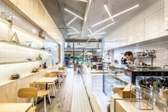 The simple palette of unadorned white tiled wall and counter to the internal layer directs attention to the actual products and service. Integration of moss and greenery injects a quirky touch to the up-and-coming café.