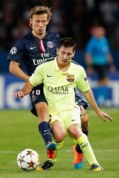 Lionel Messi of Barcelona holds the ball up against Clement Chantome of PSG during the Group F UEFA Champions League match between Paris Saint-Germain v FC Barcelona held at Parc des Princes on September 30, 2014 in Paris, France.