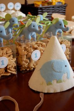 "Cute idea for first birthday party. Fill plastic square containers with animal cookies. Top with cute stuffed elephant (IKEA), tie with ribbon, and affix ""1"" round sticky label. Cheap and easy guest gifts."