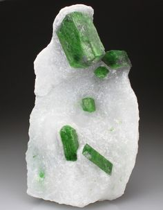 Large prismatic crystals of bright green Pargasite are revealed from the marble matrix. The Pargasite crystals measure to x and are well formed, translucent with subvitreous lustre.