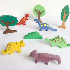 Wooden dinosaur toy set  9 piece set 5 wooden dinosaurs, 3 trees and a bush  Your child will have hours of fun playing with the figurines. The pieces are made of solid pine wood. This dinosaur set has been hand cut, painted with non-toxic paint and varnished with an organic varnish (all certified toy safe). All the pieces have been sanded and the edges rounded to make it soft for childrens little hands. All the wood comes from sustainably managed forests (FSC certified). Wooden toys are…