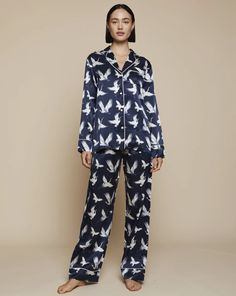 Embellished with dancing Japanese cranes Aves is a unique print symbolizing luck, marital fidelity and long life. The Elisabetha Pyjama Top in Aves is made from 100% silk satin, embellished with Mother of pearl buttons, a handsome notched collar and a breast pocket for your essentials. Look elegant as you lounge before bedtime.