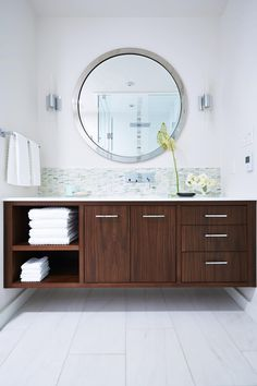 As seen on season 1 of Sarah Sees Potential, designer Sarah Richardson borrowed 15 square feet from the adjacent guest bedroom to carve out space for this spa-like bathroom vanity. To give the room a first class feel, Sarah added a large silver-framed round mirror, a mosaic tile backsplash and a floating, custom-built wood cabinet with plenty of storage space.