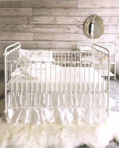 #Rustic #Luxe #nursery.  Love the pure white crib and bedding with the rough hewn walls.  The sheepskin rug brings it all together.