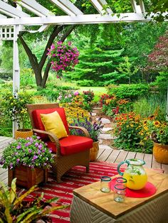 Outdoor Living space on Backyard porch. What a retreat with the amazing colors from nature. Decor furnishings colors bring out the colors from the flowers & plants. So beautiful!