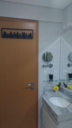 Banheiro social com espelho pantográfico, cesto de roupas inserido na marcenaria planejada, cabideiro divertido remetendo às grandes cidades.