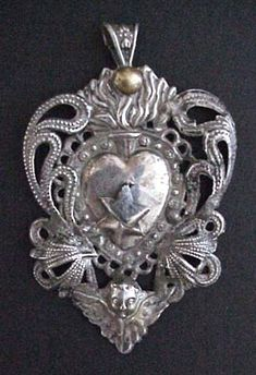 Antique Spanish Colonial Silver Ex Voto Pendant from Bolivia. | The pendant has been formed from high content sterling silver with the image of the sacred heart, or Sagrado Corazón, surrounded by traditional colonial scrollwork and an angel at the bottom.