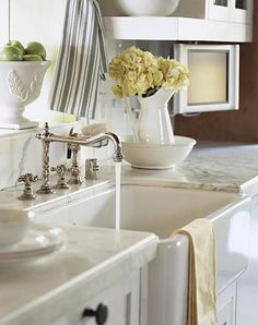 Farmhouse Sink, Vintage Look-It's not a chore to do dishes in this kitchen. A sleek, deep-basined farmhouse sink is surrounded by smooth marble countertops. Vintage-inspired fixtures continue the simple and elegant style of this kitchen