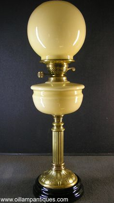 -Oil Lamp Antiques | Custard Glass Banquet Lamp The cased glass shade and font are completely matching and proportions are just right. The stem is a reeded brass column and it is set atop a brass and black glazed ceramic base. THe burner is fitted, there are two new wicks and the oval duplex chimney completes the lamp. Circa first quarter of the 20th century