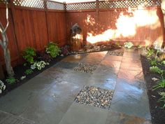 Simple Stone Patio: A single core-drilled basalt column water feature provides a corner focal point.