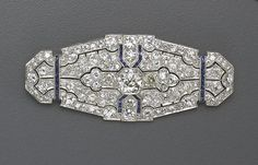An art deco diamond, sapphire and platinum brooch, circa 1925 the openwork lozenge-shaped panel, centering an old mine-cut diamond and pavé-set throughout with old mine and old European-cut diamonds, with calibré-cut sapphire detail, millegrain setting; central diamond weighing an estimated: 1.20 carats, remaining diamonds weighing an estimated: 5.00 carats.