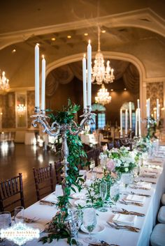 Formal candelabra used at Merion Cricket Club on long rectangular tables for drama And romance. The candelabras were entwined in Italian Ruscus and the centerpieces were created in silver cache pots featuring peonies, spray roses, stock, maiden hair fern, Nancy Saam Flowers Photo Credit: Cappy Hotchkiss Photography