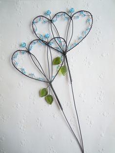 Pro holku hastrmanskou - zápich Drátovaná dekorace z černého vázacího drátu, dozdobená skleněnými korálky v barvě bleděmodré a čiré, praskanými korálky a skleněnými lístečky. Velikost květu: 10,5-11 cm x 7,5-8 cm, výška zápichu cca 34 cm. Cena za 1 kus.