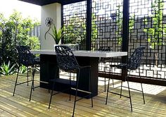 Black resin chairs with metal legs  blend with the cut metal garden privacy screen used on this deck