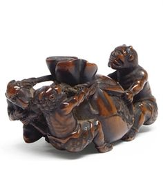 A JAPANESE WOOD NETSUKE 19TH CENTURY Carved as three oni pulling and pushing a large oversized sack of gold and coins, signed Gisaku 2 3/8in. (6cm.) wide