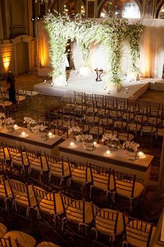 Chuppah made with wintry white blossoms accented by wispy greenery sits on a stage so guests can see the ceremony ~ Inside Weddings