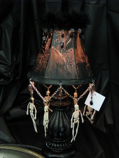 Wood table lamp I picked up from a thrift store, crackled the shade, painted and distressed bottom, added dangling skeletons and beads. The lamp looked great when lit.