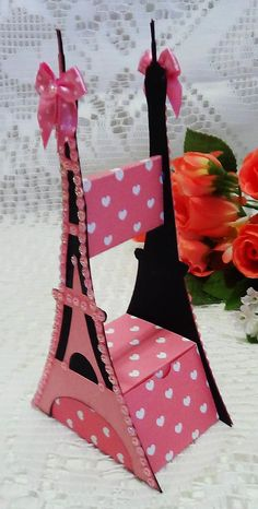 Caixinha para lembrancinha de casamento, aniversário ou debutante no formato da Torre Eiffel Confeccionado com papel 180 gr. e é toda decorada com strass e laços de cetim Pode ser feito em outras cores/ estampas. O prazo de confecção refere-se à até 20 unidades. Para quantidades maiores consu...