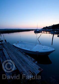 Boat leashed on a tiny jetty at Sunset in a water channel beside Sečovlje Salina Nature Park (Krajinski park Sečoveljske soline)